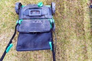 image of gardener using a lawn scarifier